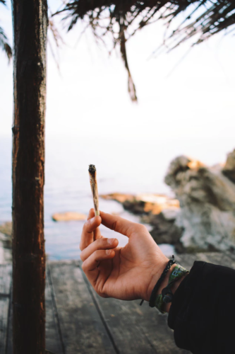 hand holding a spliff with water in background