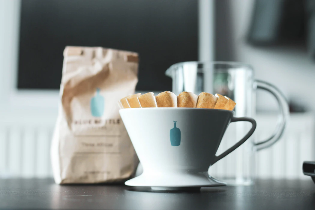 Coffee mug, bag of coffee, and clear pitcher on a gray counter