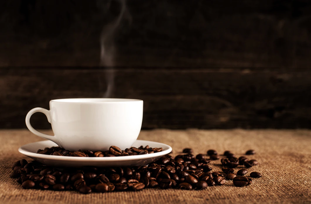 Steaming cup of CBD coffee in a white mug surrounded by coffee beans