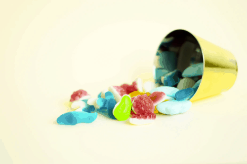 colorful cbd gummies spilling out of a cup