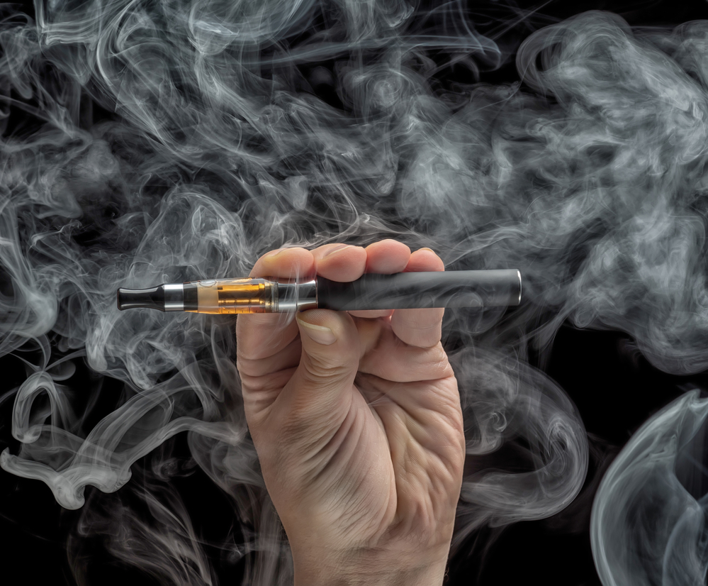 Hand holding a vape pen with smoke all around against black background