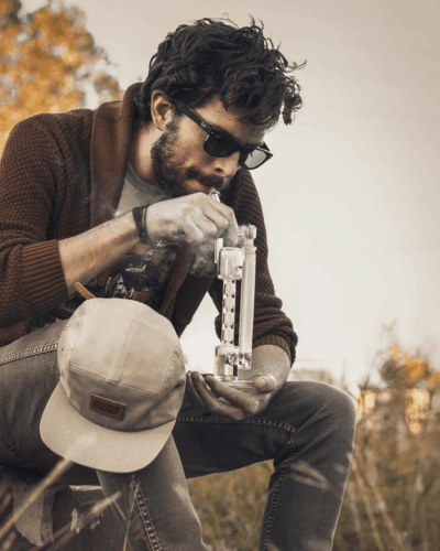 Man smoking weed outside, learning how a bong works