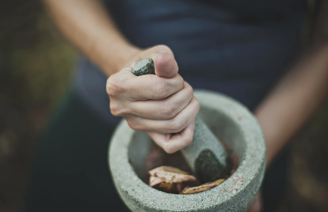 man using a mortar and pestle after learning how to grind weed without a grinder