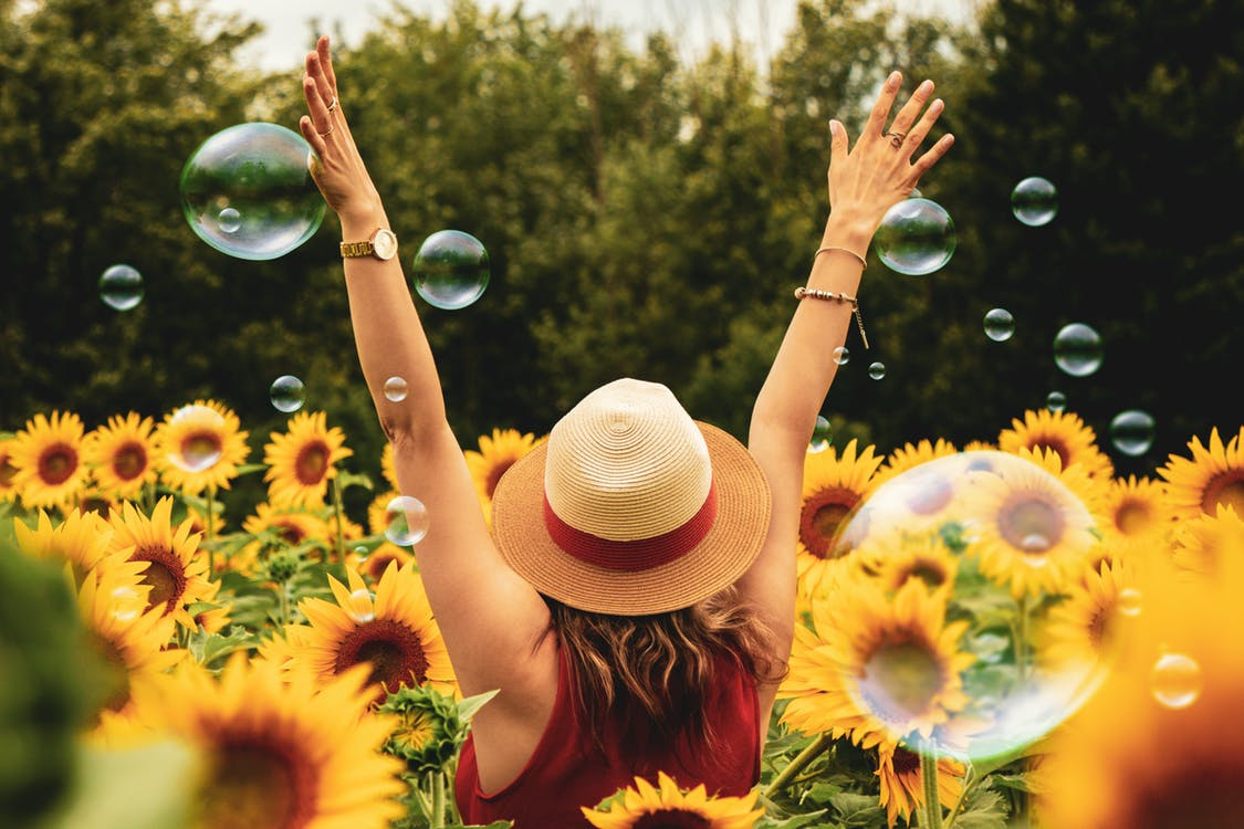 woman in a field of sunflowers with bubbles around her