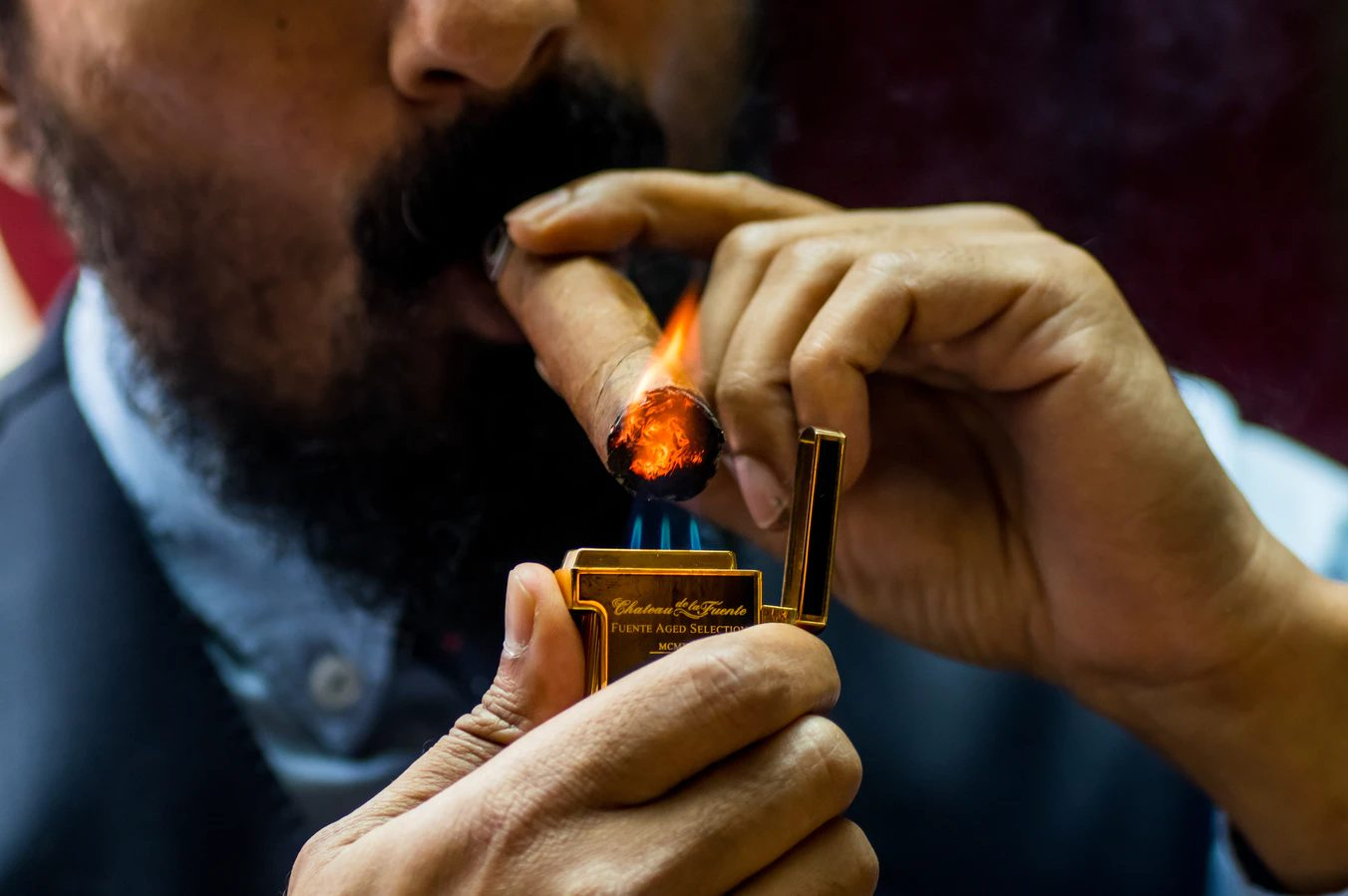 Man in a suit lighting a blunt