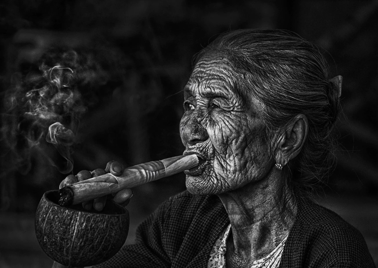 elderly Native American woman showing how to smoke a joint