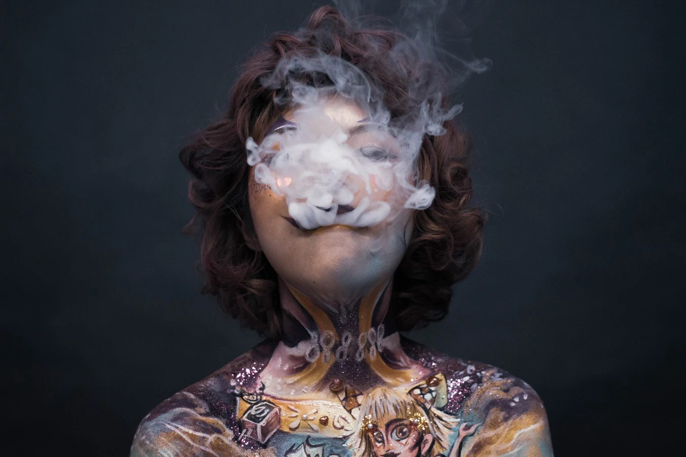 tattooed woman blowing smoke from a joint